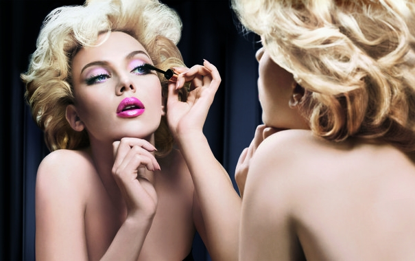 Женщина делает макияж на лице